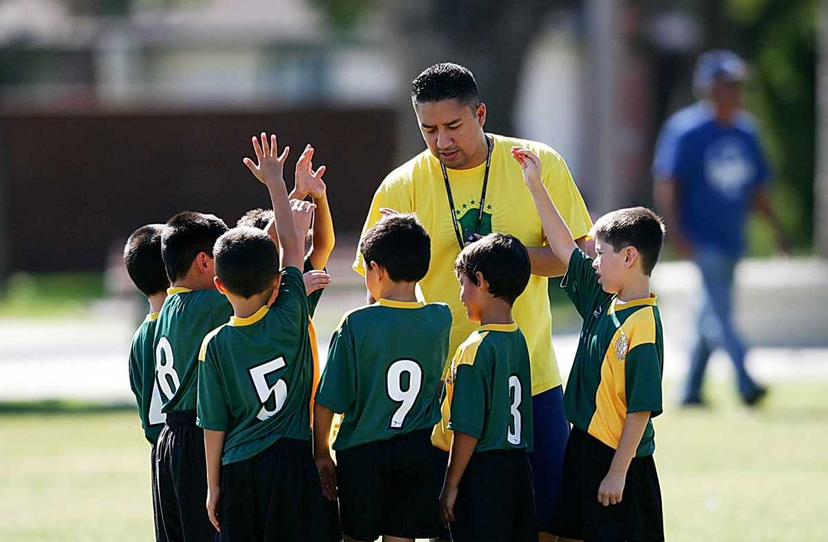A coach discusses football with youths